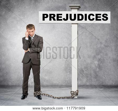 Businessman word prejudice on post sign