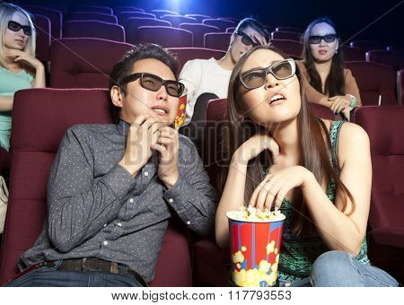 Couple sitting at the cinema, watching a horrors film. Cinema photo series