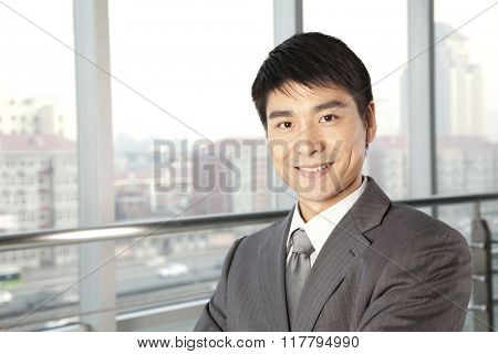 Young Businessman in front of window