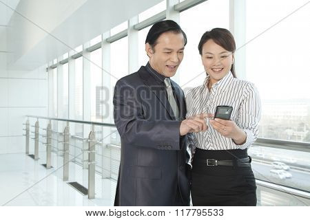 Businessman and Businesswoman looking a phone