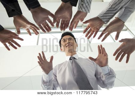 Crowd Reaching for Businessman