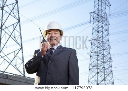 Construction manager on walkie talkie