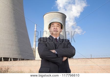 Businessman in front of cooling tower