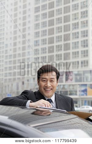 Businessman smiling, working outdoors on car