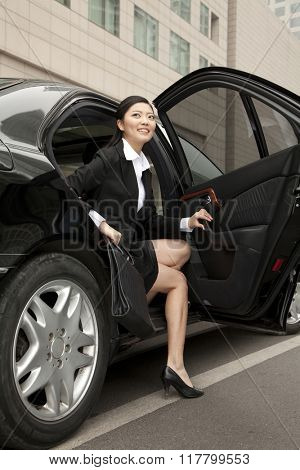 Businesswoman stepping out a car