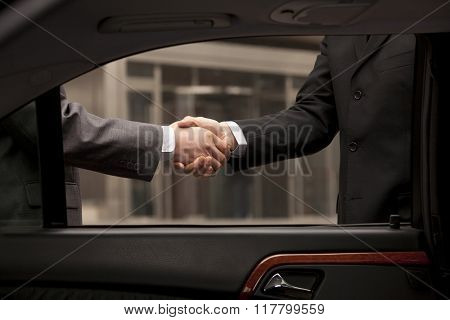 Two businessmen shaking hand through car window