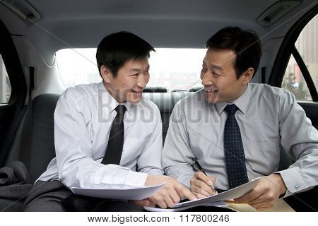 Businessmen working in back of car