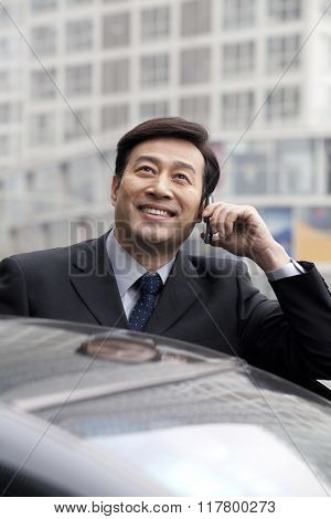 Businessman talking on phone outdoors