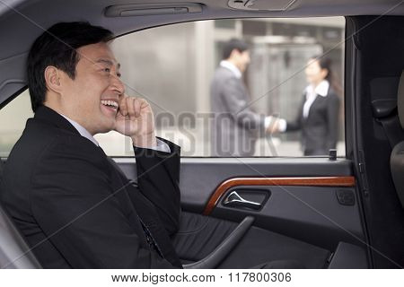 Businessman talking on phone in car