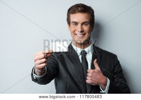 Close up photo of young attractive businessman. Businessman looking at camera, smiling and showing thumb up and visit card