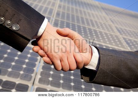 Shaking hands in front of solar panels