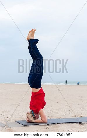 Sporty woman doing Supported Headstand, yoga asana Sirsasana, Shirshasana, Sirshasana, Headstand on