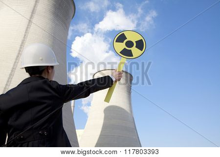 Engineer in front of cooling towers with sign