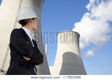 Engineer in front of cooling towers