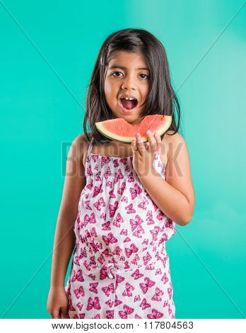 indian child girl eating watermelon isolated on green background