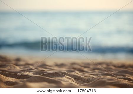 Close up of sand of beach with blurred sea background