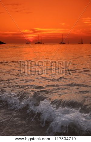 Beautiful sunset over the sea with many yachts
