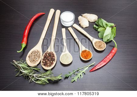 Various colorful spices on kitchen spoons on black wooden table background