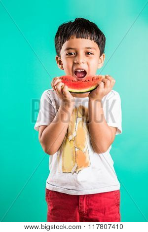 little indian boy eating watermelon isolated on green, asian boy eating watermelon