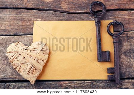 Old key with decorative heart and sheet of paper on wooden background, close up