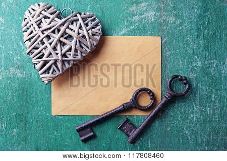 Old key with decorative heart and sheet of paper on green scratched wooden background, close up