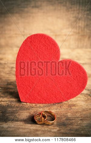 Red felt heart and wedding rings on wooden background closeup