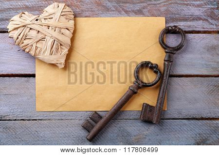 Old key with decorative heart and sheet of paper on blue wooden background, close up