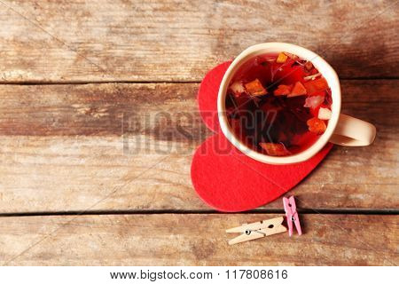 Cup of fruit tea on red heart with clothespins on wooden background closeup