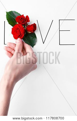 Inscription love with red roses and hand on white background