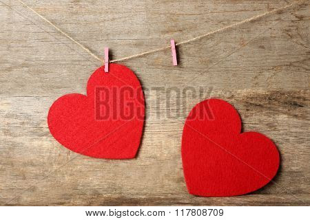 Red felt hearts hang on cord against wooden background