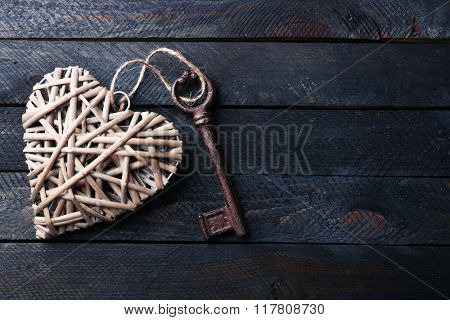 Old key with decorative heart on dark wooden background, close up