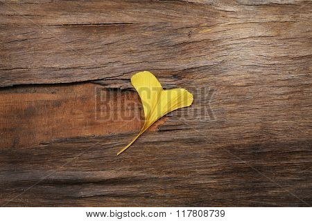Autumn leaf like a heart on wooden background