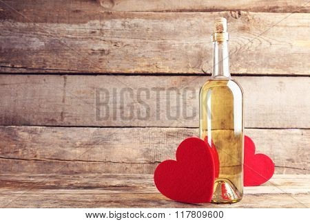 Red felt hearts with wine bottle on wooden background