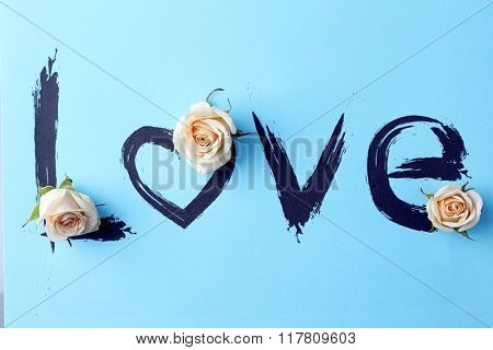Inscription love with beige roses on blue background