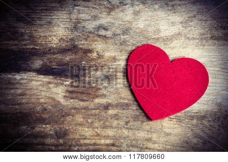 Red felt heart on wooden background
