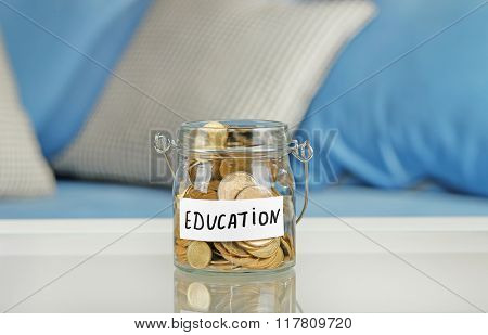 Glass jar with Ukrainian coins for education on a table