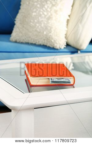 Red book with hidden dollar banknotes on glass table
