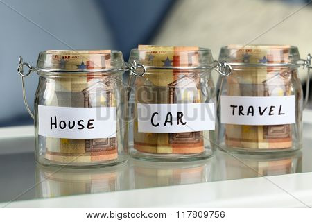 Glass jar with euro banknotes for house, car and travel on a table