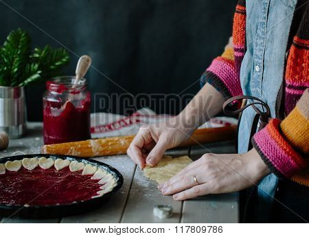 Woman prepares a berry tart in style kinfolk