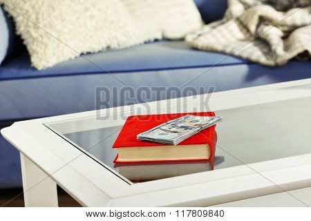 Red book with stack of dollar banknotes on glass table
