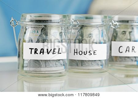 Glass jars with dollar banknotes for car, house and travel on a table