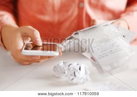 Woman with bills and smart phone at the table. Calculation of costs