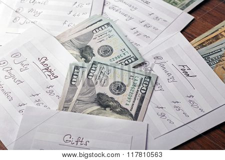 Distribution of money, financial planning, dollars in envelopes on wooden table background