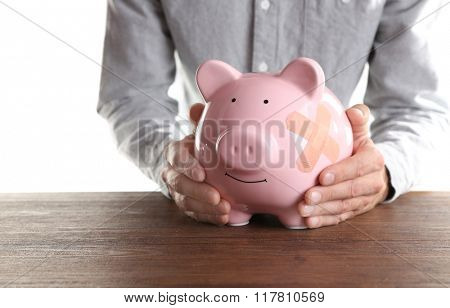 Man holding Piggy Bank with adhesive bandage, on white background