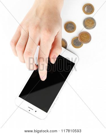 Hand with smart phone and euro coins, isolated on white. Telephone charges
