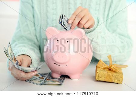 Woman putting dollar banknotes into piggy bank. Savings money for gifts concept