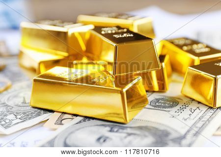 Gold bars on dollar banknotes, close up