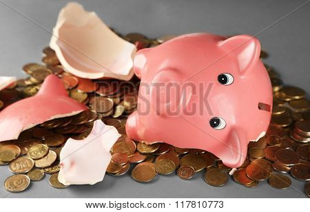 Broken piggy bank with pile of coins on grey background, close up