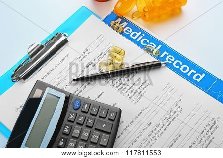 A stethoscope, pills, pen, calculator and clipboard, close-up