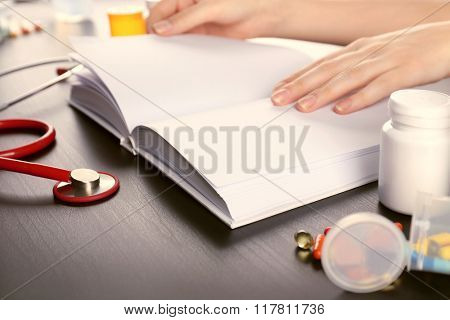 Human's hands on medical book with pills and red stethoscope, closeup
